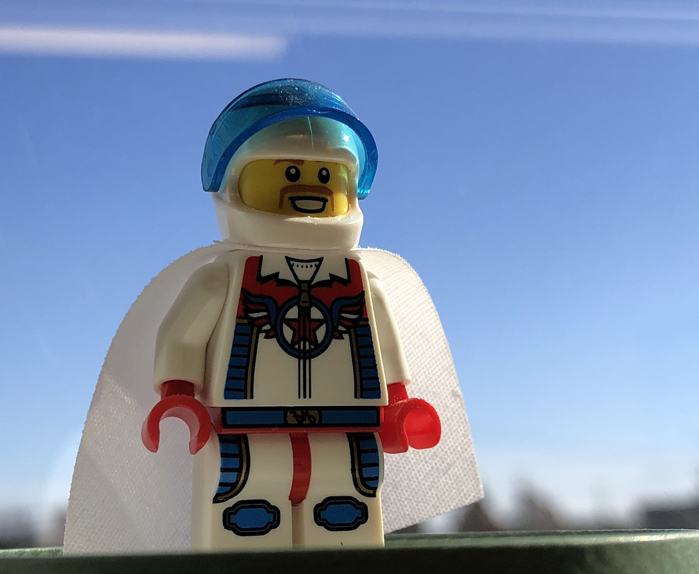 Lego mustachioed daredevil minifigure in a white jumpsuit with blue details and striping against a blue sky.